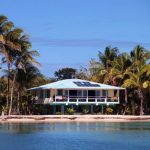 Beach house with solar panels and tropical vegetation